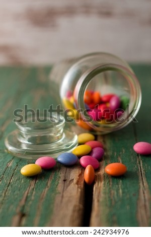 Spilled color chocolate smarties on old wooden board with worn green color with few pieces in the groove. - stock photo