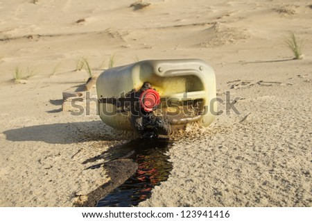 Spilled oil can on a beach - stock photo