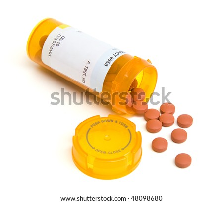 Spilled pill bottle isolated on white. - stock photo