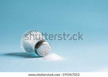 Spilled salt and saltshaker on blue background - stock photo