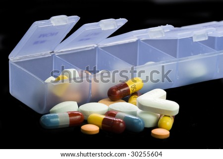 Spilled weekly vitamin/pill portion control box - stock photo