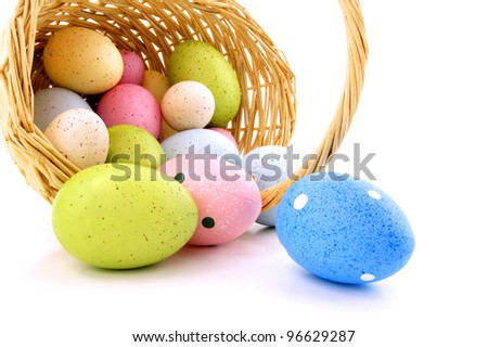 Spilling Easter basket of colorful eggs over a white background - stock photo