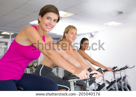 Spin class working out in a row at the gym - stock photo