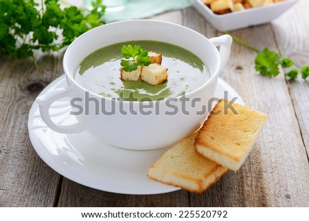 Spinach cream soup and toasts - stock photo