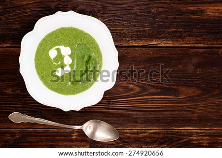 Spinach cream soup in rustic plate on wooden background, top view with copy space. Culinary soup eating.  - stock photo