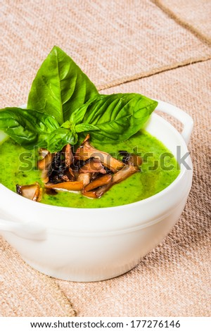 Spinach cream-soup with fried mushrooms and fresh basil - stock photo