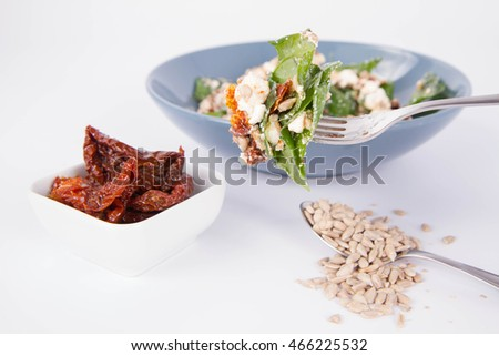 Spinach, dried tomatoes, feta cheese and sunflower seeds salad on a white background