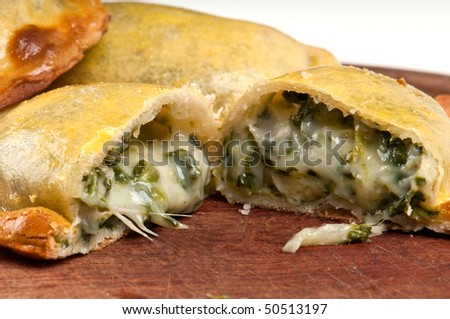 Spinach empanada fill close up.  The Empanada is a pastry turnover filled with a variety of savory ingredients and baked or fried. - stock photo