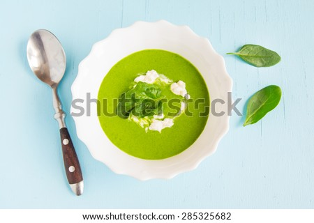 Spinach green cream soup with sour cream on blue wooden table - stock photo