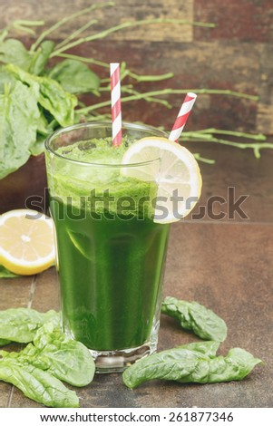 Spinach green smoothie. Green spinach smoothie in a glass with a straw, fresh leaves and lemon over dark background. Macro photograph with shallow depth of field. - stock photo