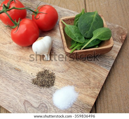 spinach in a wooden bowl group of 3 tomatoes on the vine a bulb of garlic pile of salt and pepper/whole foods 2/whole foods on cutting board - stock photo