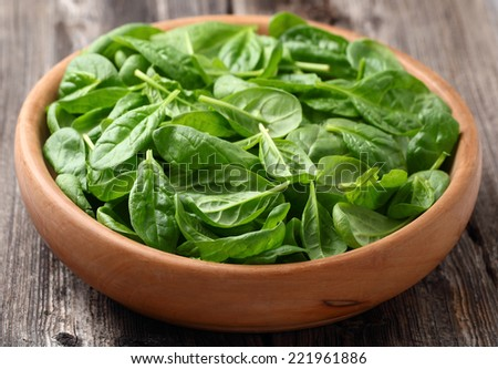 Spinach in a wooden plate - stock photo