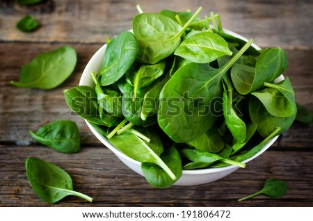 spinach in the bowl on the dark wood background. toning. - stock photo