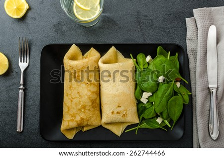 Spinach pancakes with feta cheese, simple drink with lemon, clean table - stock photo