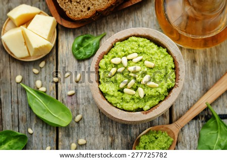 spinach pesto on a dark wood background. the toning. selective focus - stock photo