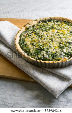 spinach quiche and vegetables with melted cheese on wooden board - stock photo