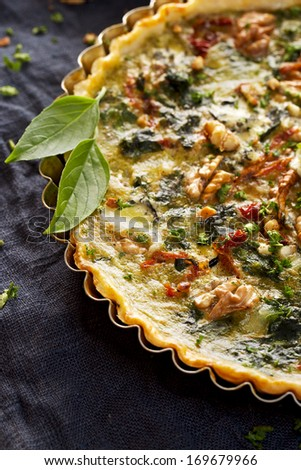 Spinach quiche with the addition of sun dried tomatoes and nuts - stock photo
