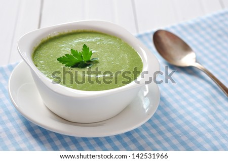 spinach soup in a bowl on a wooden background