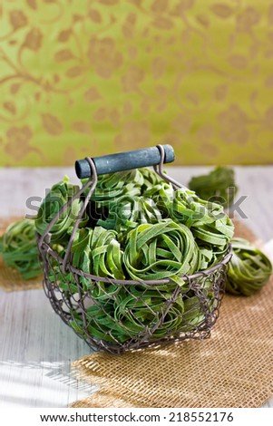 Spinach tagliatelle in a basket, selective focus - stock photo