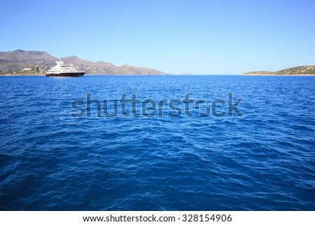 SPINALONGA, GREECE - AUGUST 18: Unidentified ferry at sea in the distance near the shore on August 18, 2015 in Spinalonga, Greece