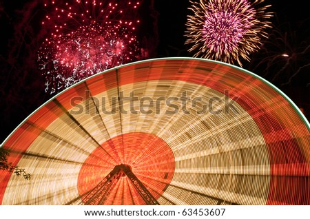 Spinning ferris wheel thrill ride. Composed over fireworks display with plenty of copy space. - stock photo
