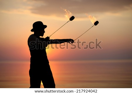 Spinning fire poi, performer silhouette on sunset background - stock photo