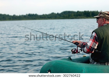 Spinning fisherman on a boat fishing - stock photo