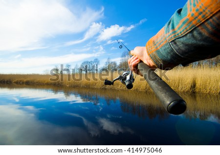 Spinning in one hand. Fisherman start to fishing by spinning on the river in sunny weather. Fishing process. Eye view  - stock photo