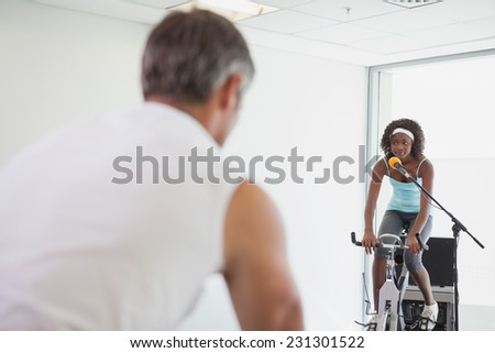 Spinning instructor motivating her class at the gym - stock photo
