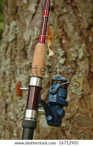 Spinning rod and reel with yellow and orange lure on a bark pine-tree background - stock photo