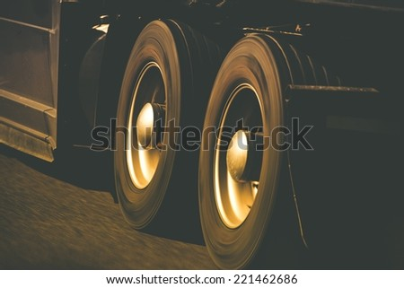 Spinning Semi Truck Wheels Closeup Photo. Browny Color Grading. Trucking and Transportation Theme. - stock photo