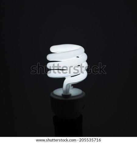 Spiral Light bulb on dark background - stock photo