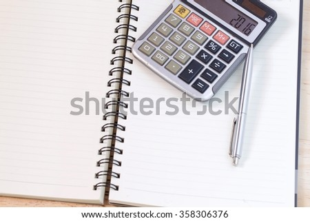 Spiral note book paper page with calculator and pen for business financial