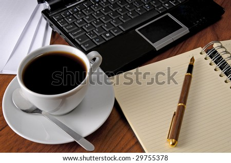 Spiral Notebook, computer and cup of coffee at workplace - stock photo