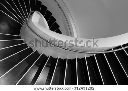 Spiral staircase in a contemporary building with interiors designed in style of minimalism. Sample image of modern architecture with distinguishing shades of black and white. - stock photo