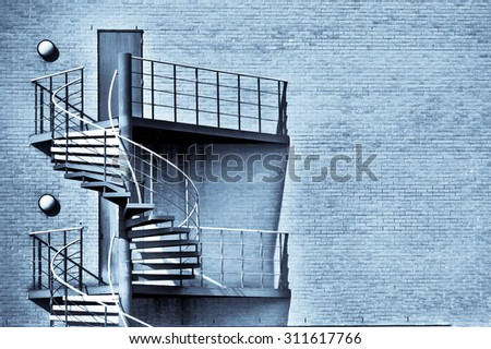 Spiral staircase on the outside of a modern building in blue tones - stock photo