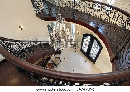 Spiral staircase with view into foyer - stock photo
