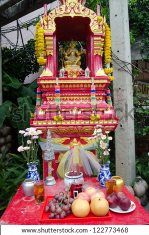Spirit house in Chiang Mai, Thailand.  Offerings of food, flowers and incense are placed to placate any gods made angry by construction nearby.  In the centre is the Hindu god Vishnu.