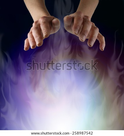 Spirit Matter - Pair of female hands hovering over a misty ethereal energy field on a black background with plenty of copy space - stock photo