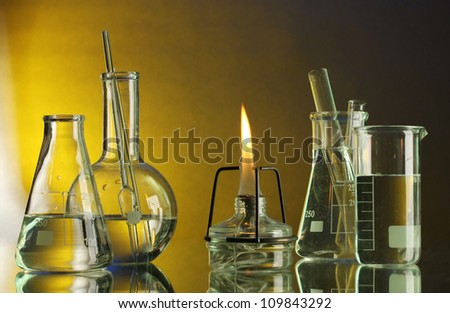 spiritlamp and test-tubes on blue-yellow background - stock photo