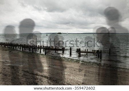 Spirits or ghosts like shadows standing on beach - stock photo