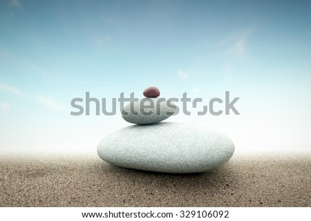 Spiritual concept background of stones tower pyramid on sand with light behind   - stock photo