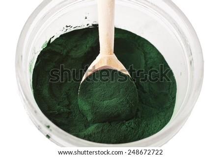 Spirulina algae powder in wooden spoon isolated on white background  - stock photo