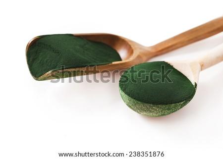 Spirulina algae powder in wooden spoons isolated on white background  - stock photo