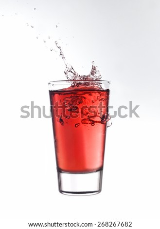 Splash in a glass of red lemonade isolated on white background - stock photo