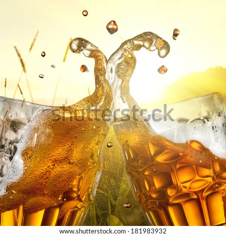 Splash of beer against wheat field and sunset - stock photo