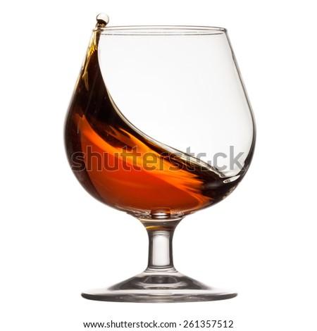 Splash of cognac in glass - stock photo