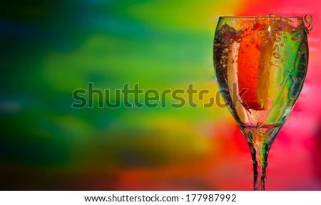 splash of drink with orange, colorful background - stock photo