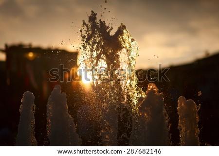 Splash of fountain against the sun on horizon. Dusk time. - stock photo