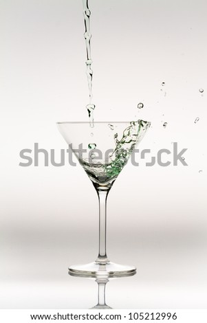 Splash of liquor inside a cocktail glass